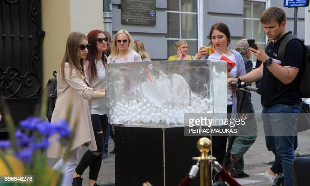 People check out an ice sculpture of Icelandic singer Bjork unveiled in Vilnius on June 16 2017 during an annual celebration to pay homage to Iceland...