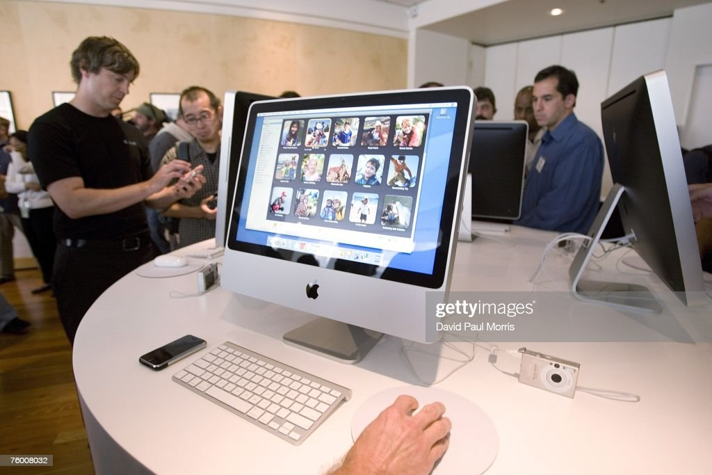 People check out the new iMac after Apple CEO Steve Jobs introduces new versions of the iMac and iLife applications August 7, 2007 in Cupertino, California. The all-in-one desktop computers now have a slimmer design in aluminum casings with faster chips and glossy screens and is up to $300 cheaper then their predecessors.