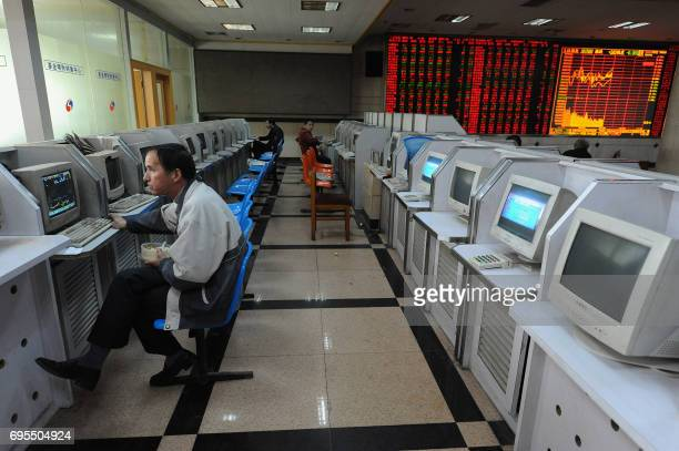 People check share prices at a securities firm in Hefei in east China's Anhui province on February 23 as Chinese stock investors are wary of the...