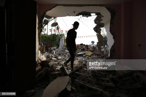 People check the remains of the house of a Palestinian who killed three Jewish residents of a nearby Israeli settlement after it was demolished by...