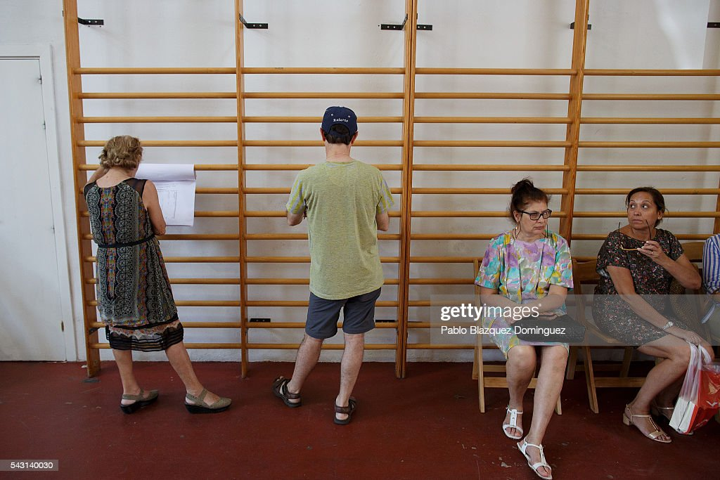 People check the voter list at a polling station during the Spanish General Elections on June 26, 2016 in Madrid, Spain. Spanish voters head back to the polls after the last election in December failed to produce a government. Latest opinion polls suggest the Unidos Podemos left-wing alliance could make enough gains to come in second behind the ruling center right Popular Party.