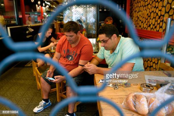 People check their smartphones in a bar behind an iron curtain as they wait after a van ploughed into the crowd killing 13 persons and injuring over...