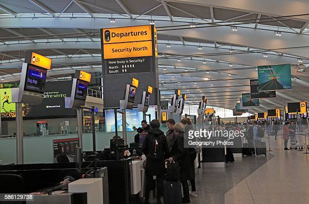 People checkingin at bag drop desk departure area terminal 5 Heathrow airport London England UK