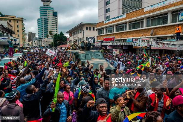 TOPSHOT People cheer a passing Zimbabwe Defense Force military vehicle during a demonstration demanding the resignation of Zimbabwe's president on...