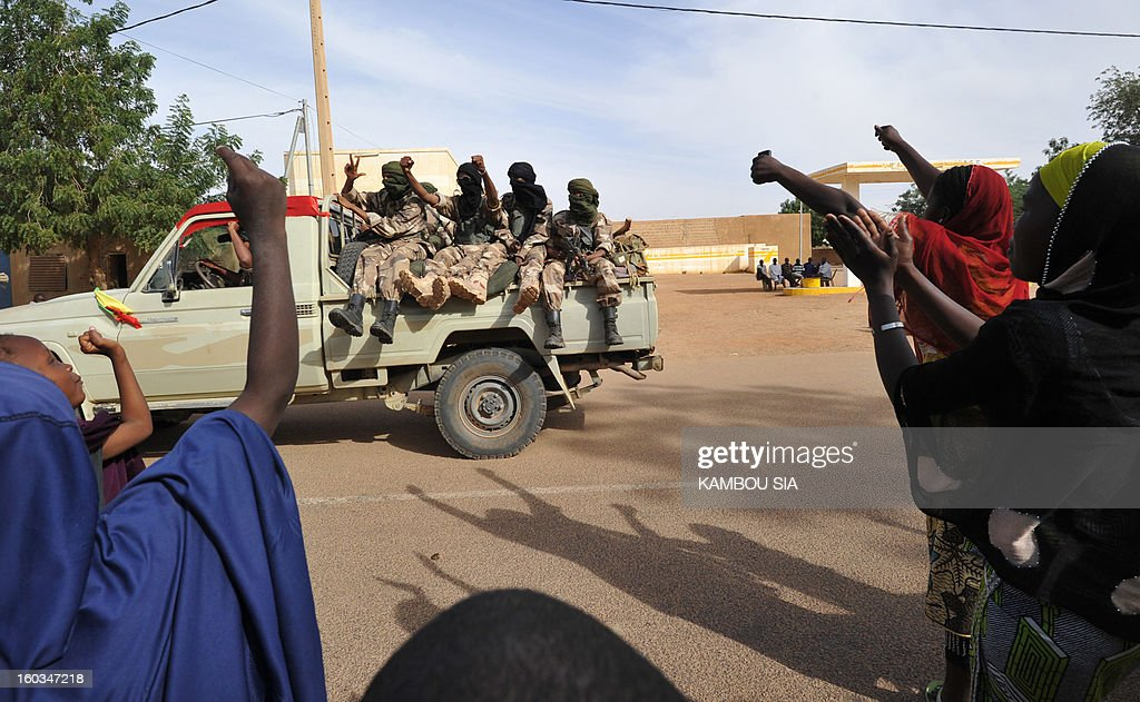 People cheer as soldiers of Malian Colonel Alaji Ag Gamou enter on January 29, 2013 Ansongo, a town south of the northern Malian city of Gao. Troops from Niger and Mali on January 29 entered Ansongo, which along with Gao was recaptured by French-led soldiers over the weekend in a lightning offensive against radicals holding Mali's north. So far, just 2,000 African troops have been sent to Mali or neighboring Niger, many of them from Chad, to boost the French-led offensive which began on January 11 and led to the recapture of several towns, including Ansongo. AFP PHOTO / KAMBOU SIA