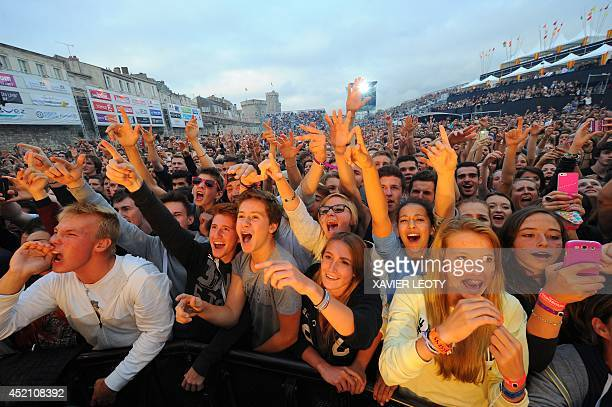 People cheer as they listen to a concert given on the main stage by French rapper Akhenaton of the band IAM on July 13 2014 in La Rochelle during the...