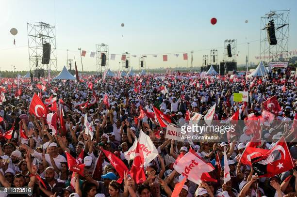 People cheer as Turkey's main opposition Republican People's Party leader Kemal Kilicdaroglu throws flowers to supporters during a rally on July 9...
