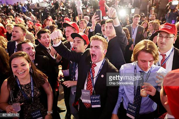 People cheer as voting results for Florida come in at Republican presidential nominee Donald Trump's election night event at the New York Hilton...