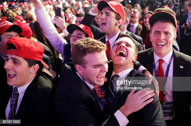 People cheer as voting results for Iowa come in at Republican presidential nominee Donald Trump's election night event at the New York Hilton Midtown...