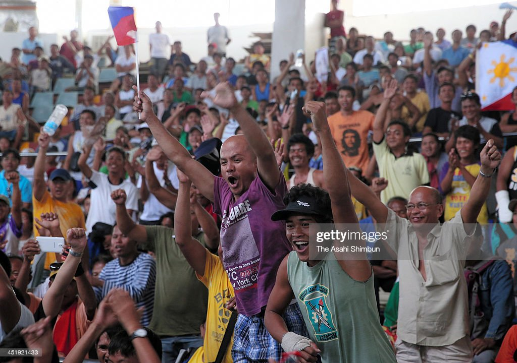 People cheer during the public viewing of the WBO International Welterweight title bout of the Philippine's hero boxer Manny Pacquiao, who had told to donate the prize money to the typhoon devastated cities, on November 24, 2013 in Tacloban, leyte, Philippines. Bodies continue to be recovered nearly two weeks after the devastating Typhoon Haiyan as the official death toll now exceeds 5,000. The typhoon, which ripped through the Philippines over a week ago, has been described as one of the most powerful typhoons ever to hit land, leaving thousands dead and hundreds of thousands homeless. Countries all over the world have pledged relief aid to help support those affected by the typhoon, but damage to the airport and roads have made moving the aid into the most affected areas very difficult. With dead bodies left out in the open air and very limited food, water and shelter, health concerns are growing.