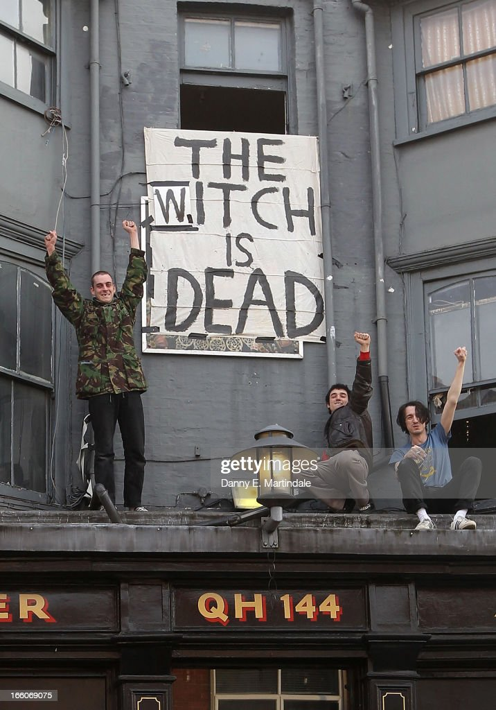 People cheer in front of a banner displaying the message 'The Witch is Dead' as they celebrate the death of former British Prime Minister Margaret...