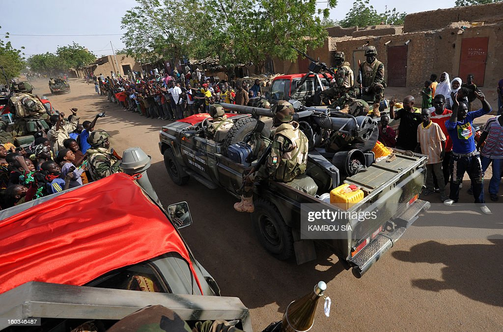 People cheer on the side of the road on January 29, 2013 in Ansongo, a town south of the northern Malian city of Gao, as Niger troops enter the city. Troops from Niger and Mali on January 29 entered Ansongo, which along with Gao was recaptured by French-led soldiers over the weekend in a lightning offensive against radicals holding Mali's north. So far, just 2,000 African troops have been sent to Mali or neighboring Niger, many of them from Chad, to boost the French-led offensive which began on January 11 and led to the recapture of several towns, including Ansongo.