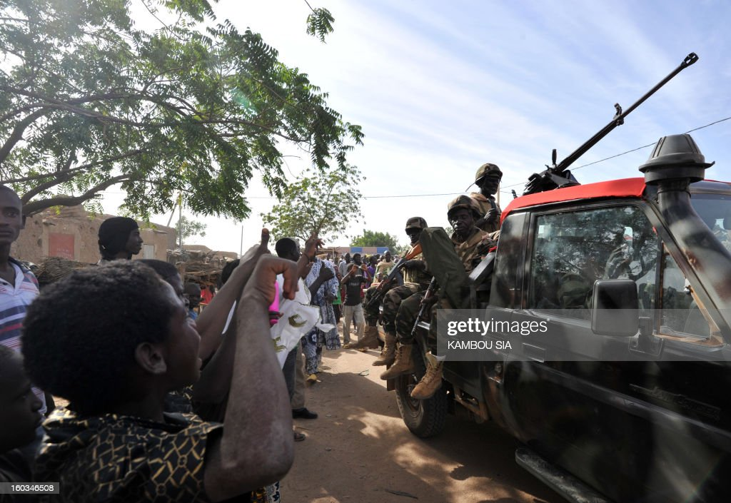 People cheer on the side of the road on January 29, 2013 in Ansongo, a town south of the northern Malian city of Gao, as Niger troops enter the city. Troops from Niger and Mali on January 29 entered Ansongo, which along with Gao was recaptured by French-led soldiers over the weekend in a lightning offensive against radicals holding Mali's north. So far, just 2,000 African troops have been sent to Mali or neighboring Niger, many of them from Chad, to boost the French-led offensive which began on January 11 and led to the recapture of several towns, including Ansongo. AFP PHOTO / KAMBOU SIA