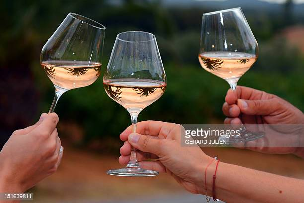 JEANNEAU People cheer with glasses of rose wine on August 28 2012 at the Chateau SainteMarguerite vineyard in La LondelesMaures France is the world's...