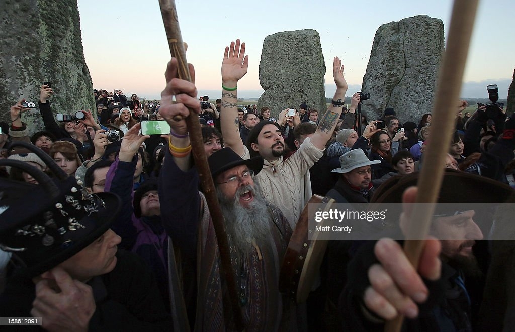 People cheers as the sun rises as druids, pagans and revellers celebrate the winter solstice at Stonehenge on December 21, 2012 in Wiltshire, England. Predictions that the world will end today as it marks the end of a 5,125-year-long cycle in the ancient Maya calendar, encouraged a larger than normal crowd to gather at the famous historic stone circle to celebrate the sunrise closest to the Winter Solstice, the shortest day of the year.