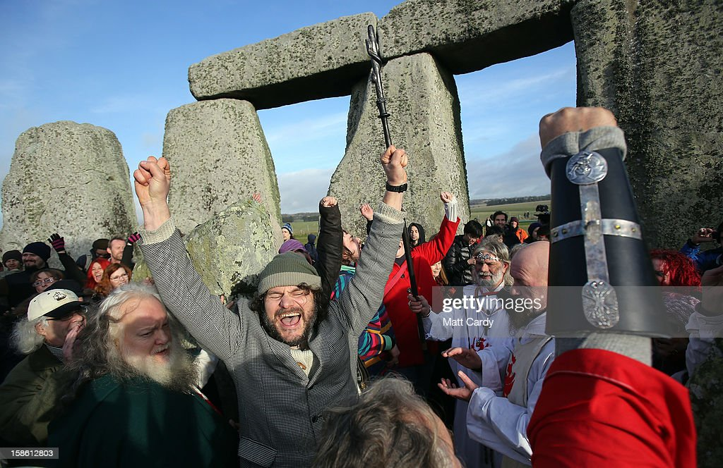 People cheers as the time passes 11.11am, the time the Mayan Apocalypse was supposed to occur, at a ceremony following the traditional winter solstice celebrations at Stonehenge, on December 21, 2012 in Wiltshire, England. Predictions that the world will end today as it marks the end of a 5,125-year-long cycle in the ancient Maya calendar, encouraged a larger than normal crowd to gather at the famous historic stone circle to celebrate the sunrise closest to the Winter Solstice, the shortest day of the year.