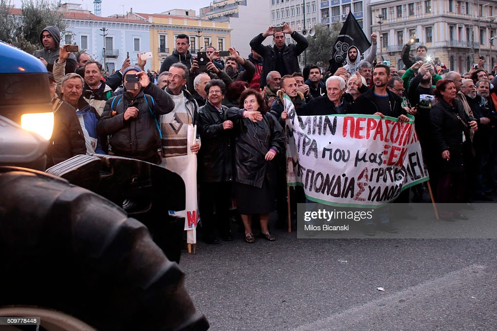 People cheers farmers while they drive their tractors during a protest on February 12, 2016 in Athens, Greece. Farmers from across Greece gather in Athens for a two-day protest against the government and its plans to impose new tax hikes and pension charges.