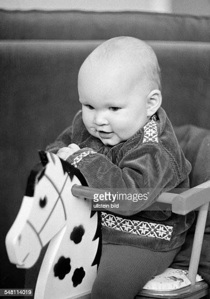 people children baby sits on a rockinghorse laughing aged 6 to 12 months aged 1 year Christina