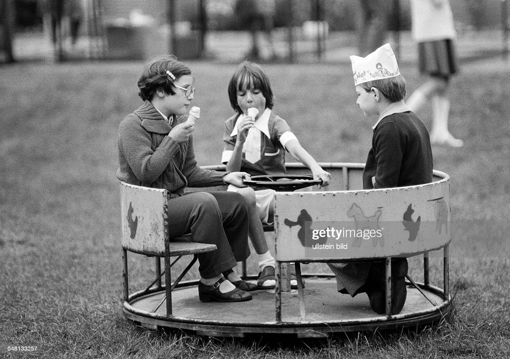 people children childrens treat two girls and a boy with a paper cap on his head sit in a roundabout and lick ice cream aged 5 to 8 years