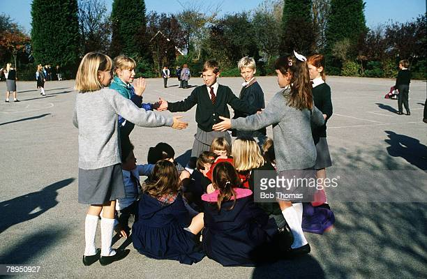 People Children Education Northamptonshire England pic circa 1990 Children in a school playground form a circle as they enjoy a game