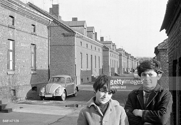 people children two boys posing at a housing estate pithead buildings colony Eisenheim in front of a house stands a car VW Volkswagen Beetle Turks...