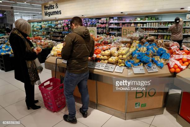 People choose fruits and vegetables at the Bio fresh section of an hypermarket store of French retail giant Carrefour in VilleneuvelaGarenne near...
