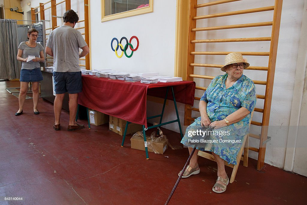 People choose their ballots as a woman sits next by at a polling station during the Spanish General Elections on June 26, 2016 in Madrid, Spain. Spanish voters head back to the polls after the last election in December failed to produce a government. Latest opinion polls suggest the Unidos Podemos left-wing alliance could make enough gains to come in second behind the ruling center right Popular Party.