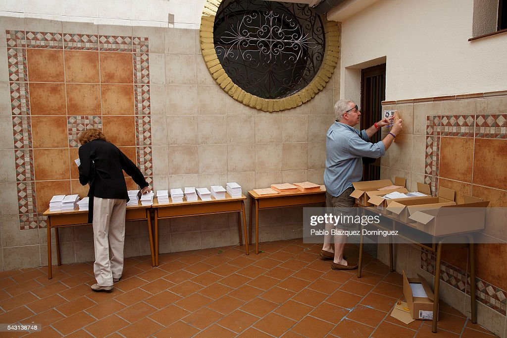 People choose their ballots to vote at a polling station during the Spanish General Elections on June 26, 2016 in Madrid, Spain. Spanish voters head back to the polls after the last election in December failed to produce a government. Latest opinion polls suggest the Unidos Podemos left-wing alliance could make enough gains to come in second behind the ruling center right Popular Party.
