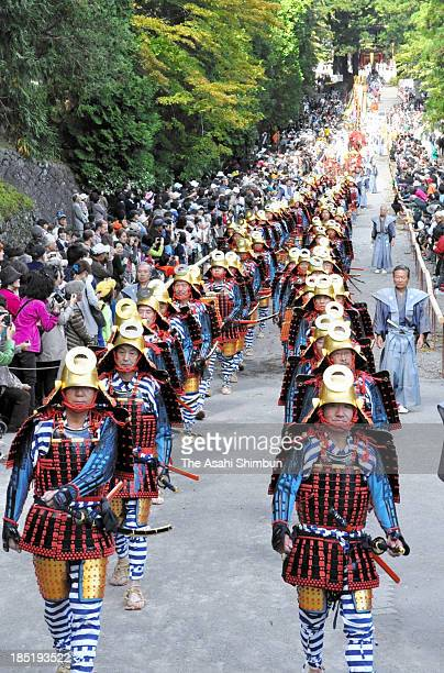 People clad traditional samurai warriors march on the main approach of the Nikko Toshogu Shrine during its Autumn Festival on October 17 2013 in...