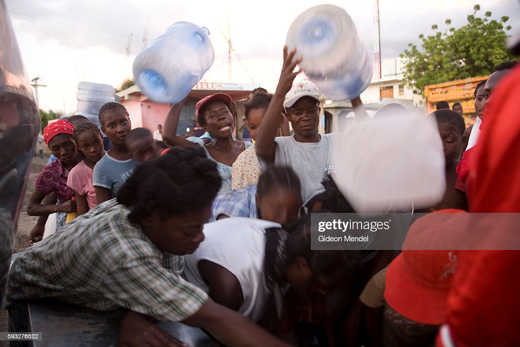 People clamour for drinking water in the centre of the city of Gonaives two weeks after it was flooded during Hurricanes Ike and Hanna They were...