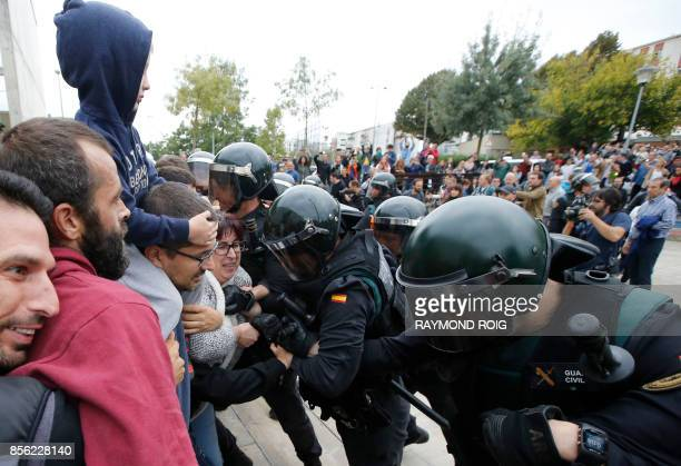People clash with Spanish Guardia Civil guards outside a polling station in Sant Julia de Ramis where Catalan president was supposed to vote on...
