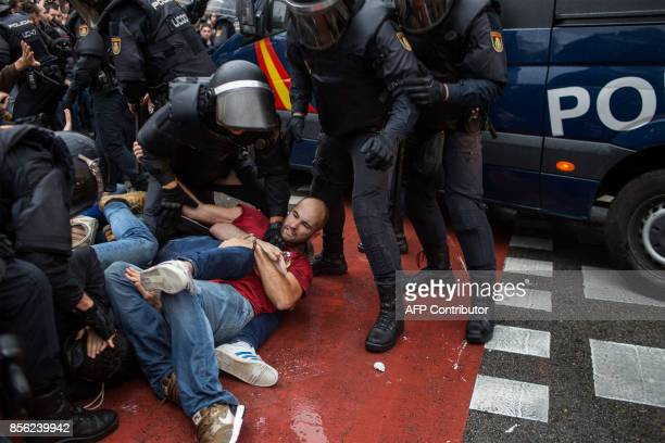 People clash with Spanish police officers outside the Ramon Llull polling station in Barcelona October 1 2017 during a referendum on independence for...
