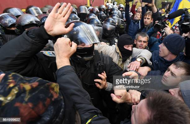 TOPSHOT People clash with Ukrainian riot policemen during a demonstration of opposition's supporters in front of the Ukrainian Parliament in Kiev on...