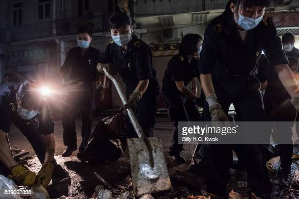 People clean debris after Typhoon Hato hits Macau on August 23 2017 in Macau China The death toll in Macau from Typhoon Hato rose to nine on Friday...