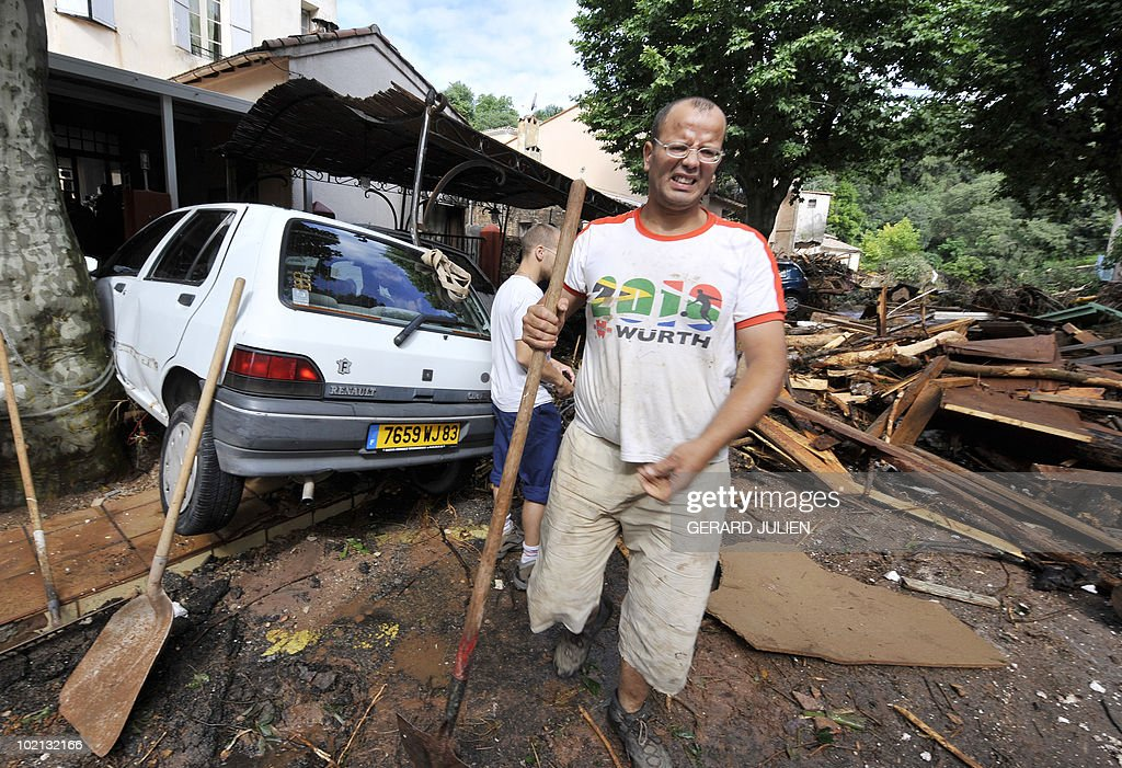 People clean the damages in the aftermath of flooding in a western district of the French south eastern city of Les Arcs sur Argens (Var) on June 16, 2010. At least eleven people have been killed by flash floods in Draguignan and in the neighboring city of Luc, caused by heavy rains.