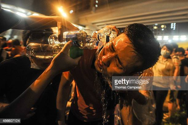 People clean the face of a protester after he was sprayed with pepper spray during a prodemocracy protest in the Kowloon district of Hong Kong on...