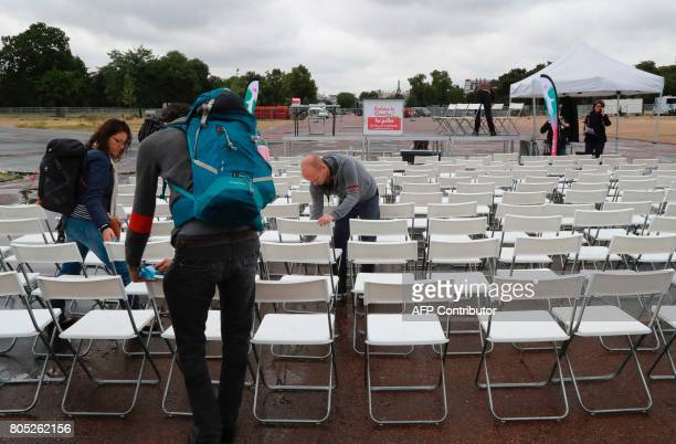 People clean the seats after the rain prior to a rally for the launch of a movement led by French Socialist member Benoit Hamon in Reuilly on July 1...