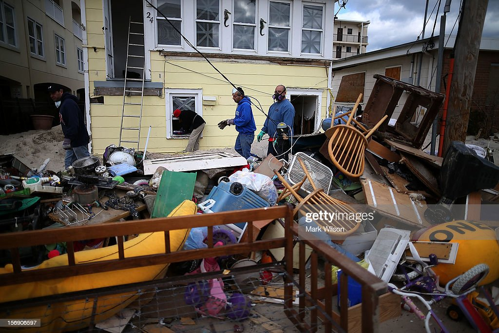 People clean trash out of a home damaged by Superstorm Sandy, on November 24, 2012 in Seaside Heights, New Jersey. New Jersey Gov. Christie estimated that Superstorm Sandy cost New Jersey $29.4 billion in damage and economic losses.