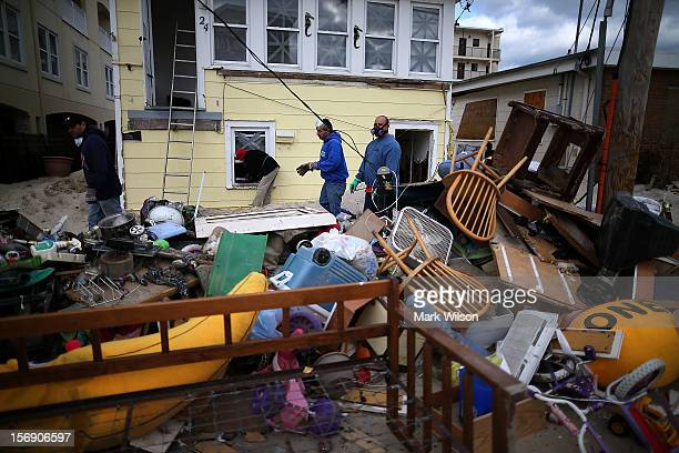 People clean trash out of a home damaged by Superstorm Sandy on November 24 2012 in Seaside Heights New Jersey New Jersey Gov Christie estimated that...