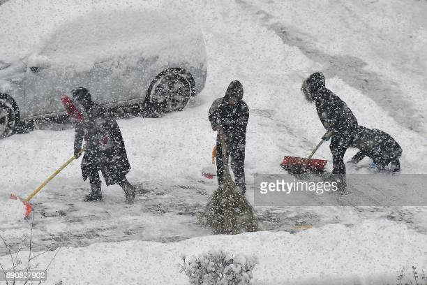 People clean up the road during snowfall in Yantai in China's eastern Shandong province on December 12 2017 A blue alert for a snowstorm and a yellow...