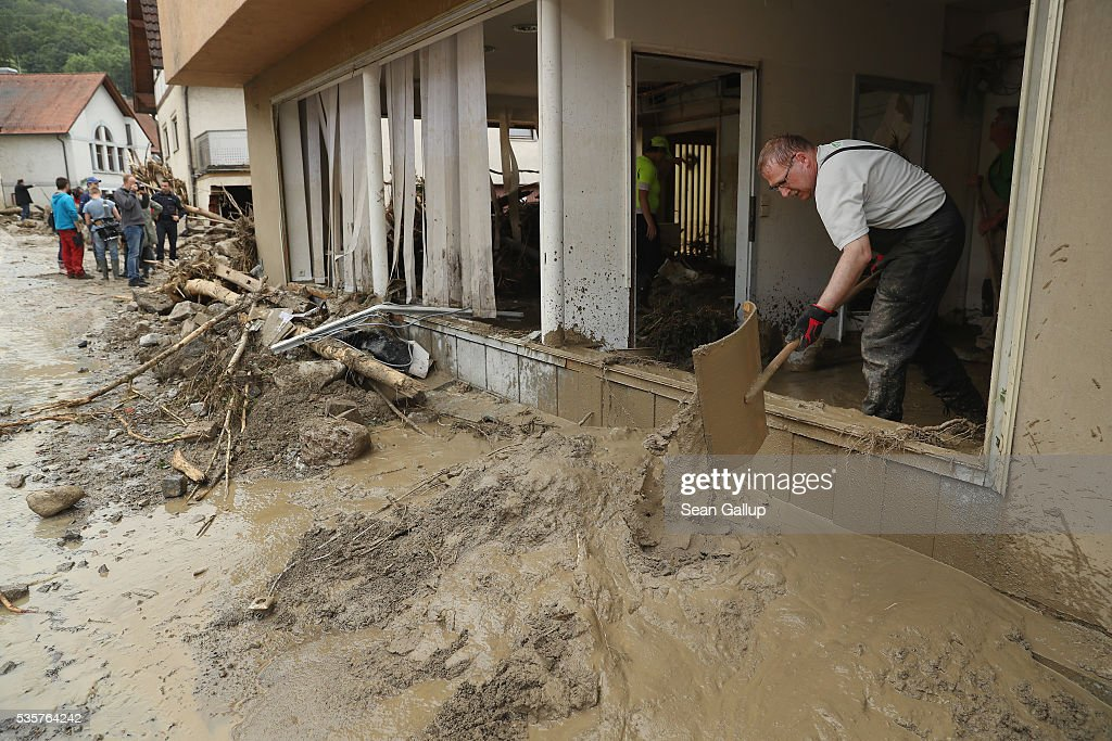 People clear mud from a flooded store in the village center following a furious flash flood the night before on May 30, 2016 in Braunsbach, Germany. The flood tore through Braunsbach, crushing cars, ripping corners of houses and flooding homes during a storm that hit southwestern Germany. Miraculously no one in Braunsbach was killed, though three people died as a result of the storm in other parts of the country.