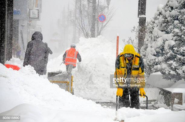 People clear snow on the street on January 18 2016 in Kushiro Hokkaido Japan