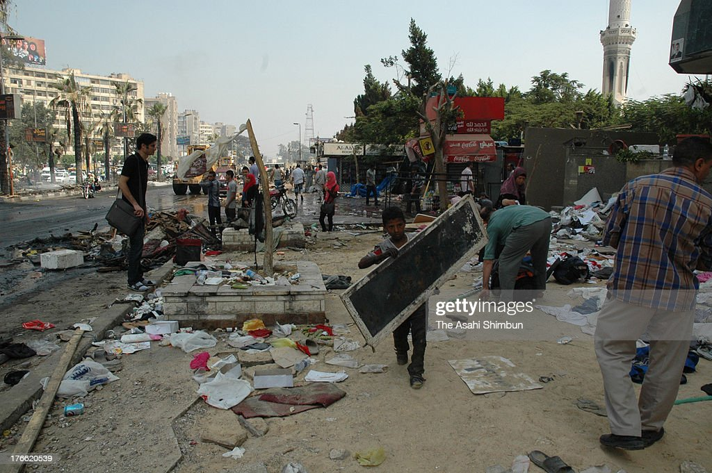 People clear the ruins outside the Rabaa alAdaweya Mosque in Nasr City on August 15 2013 in Cairo Egypt An unknown number of proMorsi protesters were...