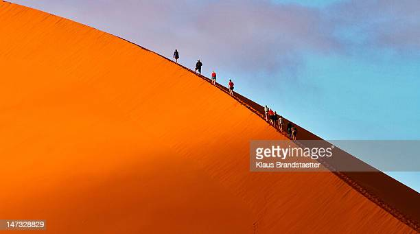 People climbing huge dune