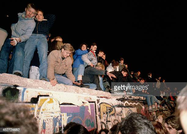 People climbing on the Berlin Wall after opening of the border on November 09 in Berlin Germany The year 2014 marks the 25th anniversary of the fall...