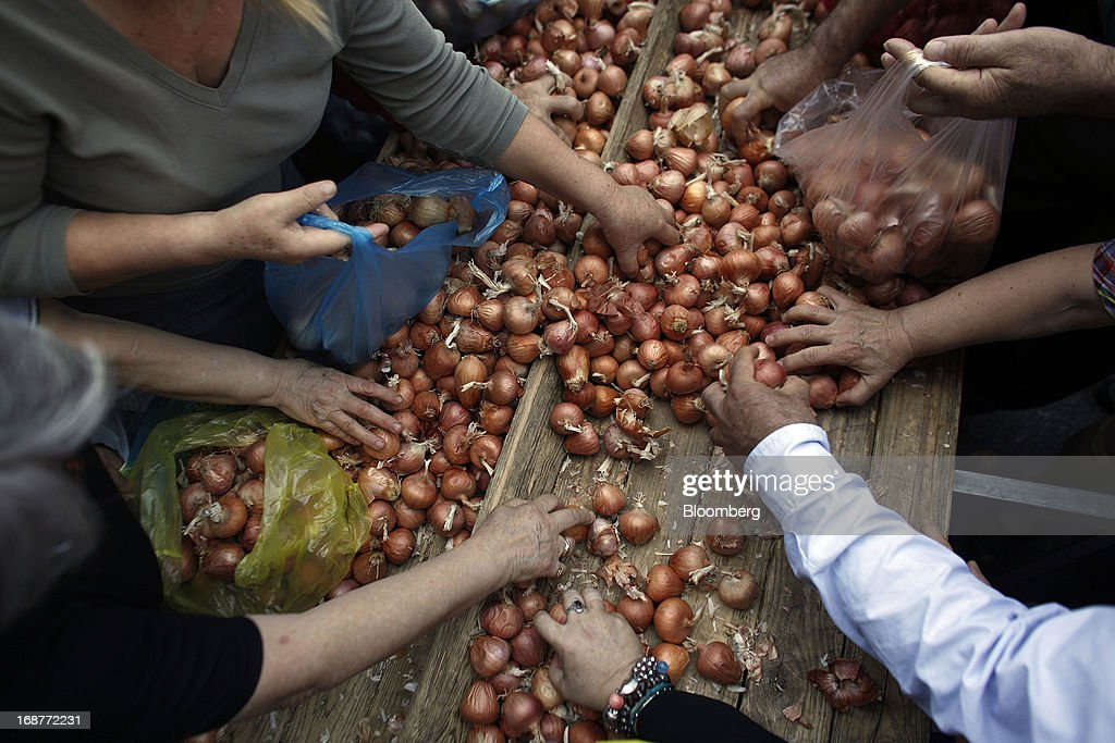 People collect free onions from a stall during a handout of leftover food by striking street vendors in Athens, Greece, on Wednesday, May 15, 2013. Greece's plans to return to international bond markets next year reflect the government's confidence it can draw a line under the country's debt crisis although the cost of borrowing suggests that might be premature. Photographer: Kostas Tsironis/Bloomberg via Getty Images