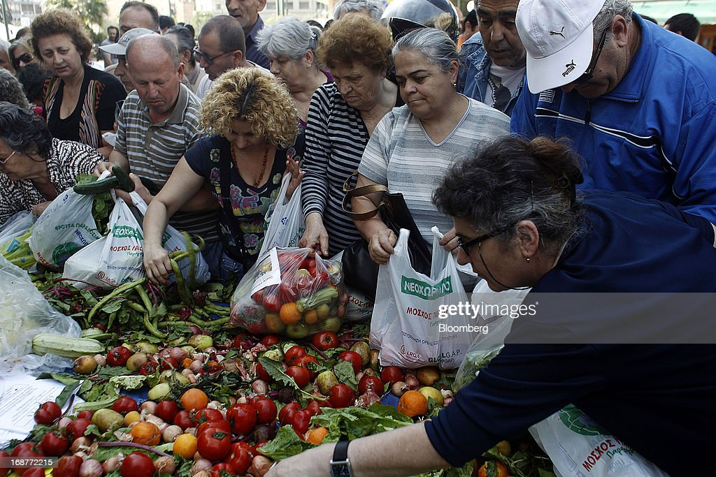People collect free vegetables from a stall during a handout of leftover food by striking street vendors in Athens, Greece, on Wednesday, May 15, 2013. Greece's plans to return to international bond markets next year reflect the government's confidence it can draw a line under the country's debt crisis although the cost of borrowing suggests that might be premature. Photographer: Kostas Tsironis/Bloomberg via Getty Images