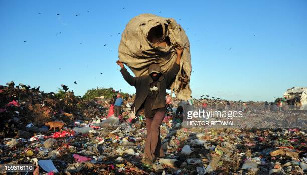 People collect plastics and metals to be sold for recycling at Managua's landfill 'La Chureca' on January 10 2013 AFP PHOTO/Hector RETAMAL