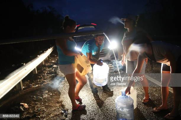 People collect spring water in containers from a pipe along side a highway since they have no running water in their home after Hurricane Maria...