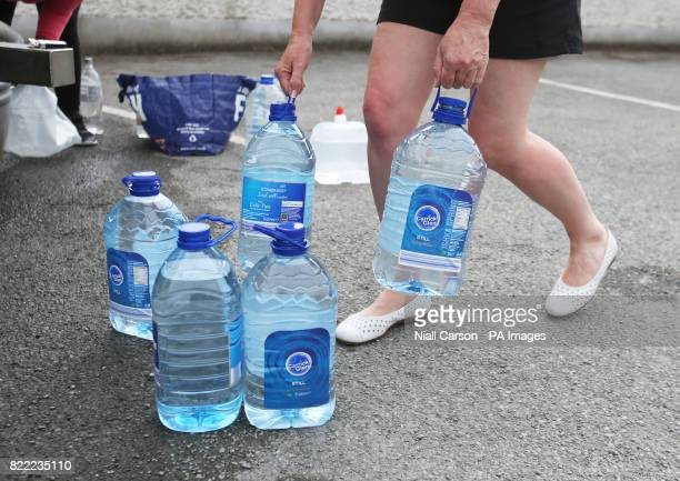 People collect water from a Northern Ireland Water Tanker outside Termonfeckin national school Drogheda after a pipe burst